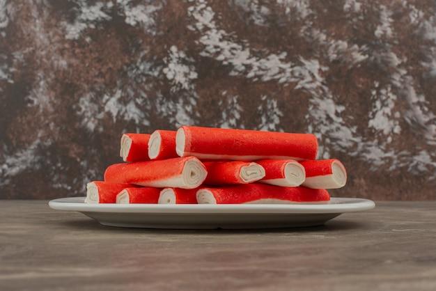 Assiette blanche avec bâtonnets de crabe.
