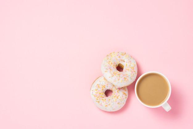 Assiette blanche avec des beignets sucrés savoureux frais sur fond rose. concept de boulangerie, pâtisseries fraîches, délicieux petit déjeuner, restauration rapide, café. mise à plat, vue de dessus