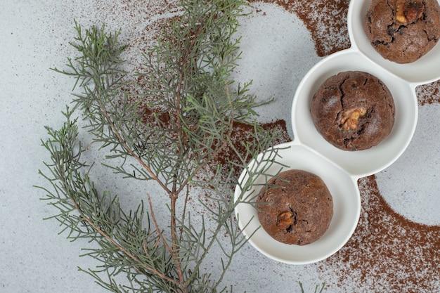 Une assiette blanche avec des biscuits au chocolat avec du cacao en poudre