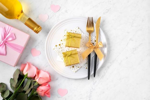 Assiette blanche avec cadeau et fleur rose rose sur fond de table en marbre blanc pour la saint-valentin