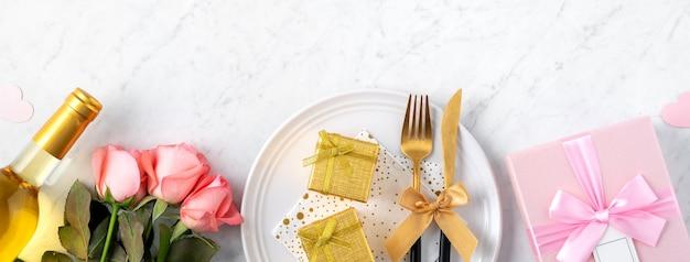 Assiette blanche avec cadeau et fleurs roses roses pour la saint valentin