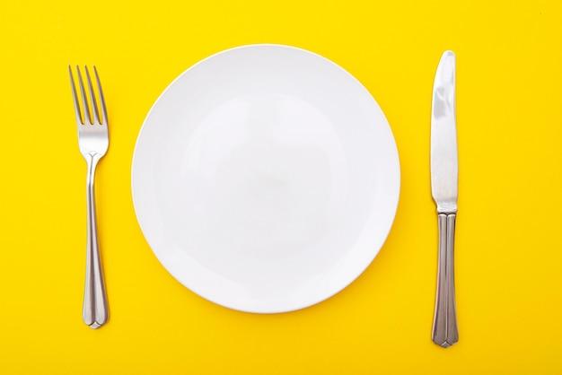 Assiette blanche en céramique avec couteau et fourchette sur surface jaune, table de cuisine, disposition, vue de dessus, espace pour le texte