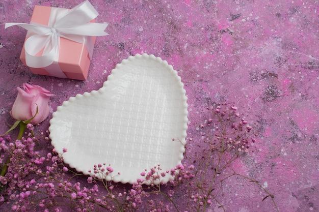 Assiette blanche avec des coeurs sur fond de fleurs roses et un cadeau emballé.