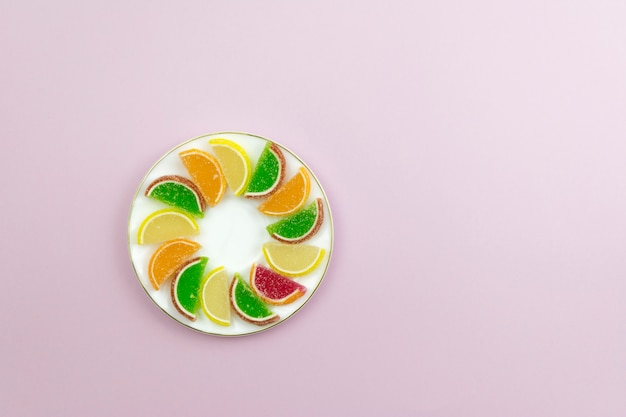 Sur une assiette blanche confiture colorée en forme de tranches d'agrumes