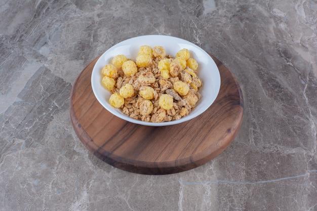 Une assiette blanche de cornflakes sains sur une planche ronde en bois.