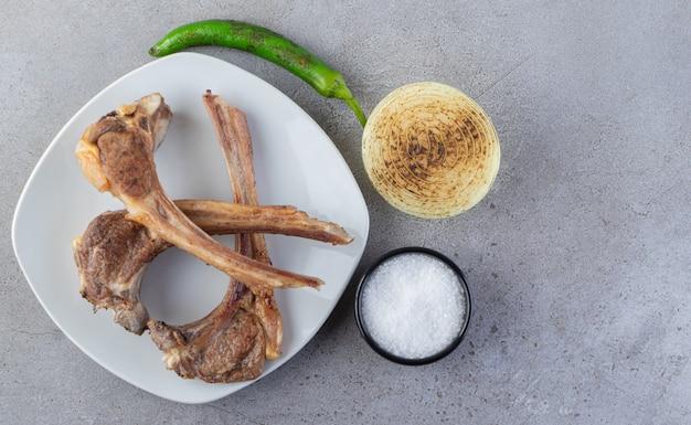 Assiette blanche de côtelettes d'agneau crues sur table en pierre.