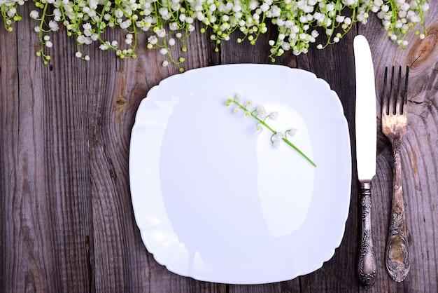 Assiette blanche avec des couverts de fer vintage sur une surface en bois grise