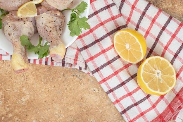 Une assiette blanche de cuisses de poulet avec des tranches de citron