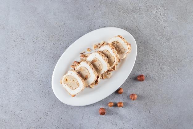 Assiette blanche de délices sucrés aux noix sur fond de pierre.