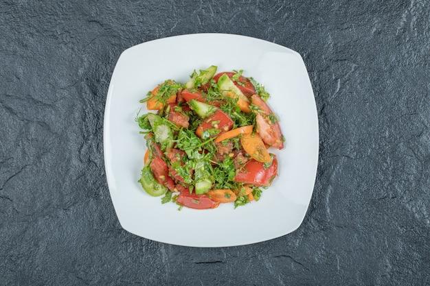 Une assiette blanche de délicieuse salade de légumes.