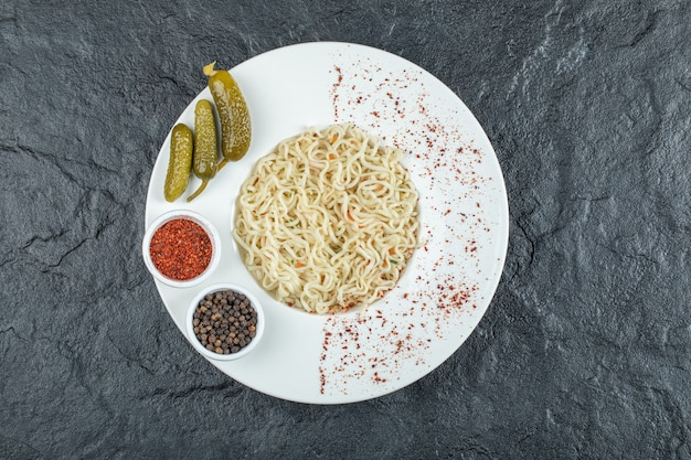 Une assiette blanche avec de délicieuses nouilles et cornichons marinés.
