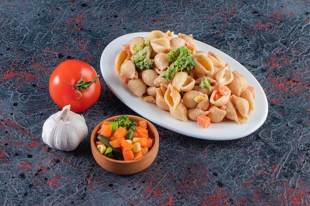 Assiette blanche de délicieuses pâtes aux coquillages et salade fraîche sur une surface en marbre.