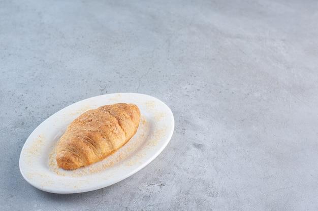 Une assiette blanche de délicieux croissants sucrés sur fond bleu.