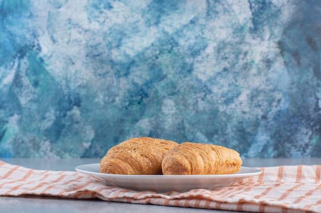 Une assiette blanche de délicieux croissants sucrés sur nappe à rayures.