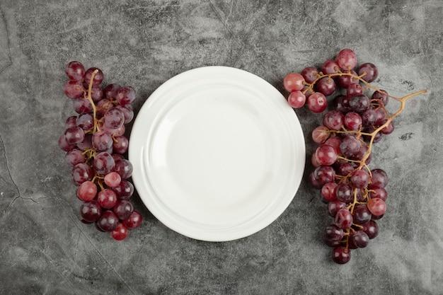 Assiette blanche et délicieux raisins rouges sur table en marbre.