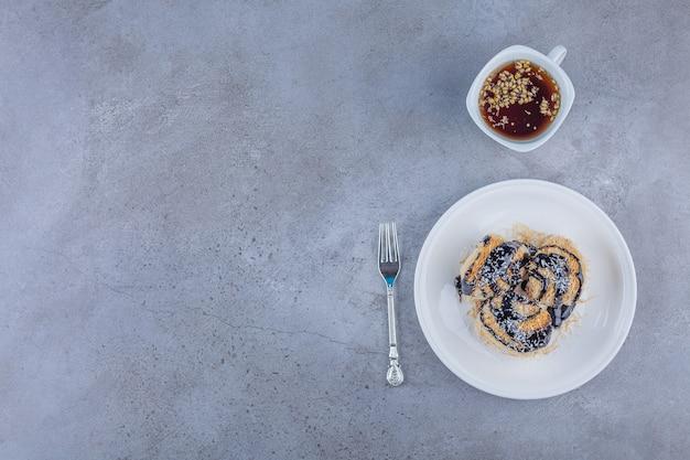 Assiette blanche de dessert au chocolat avec tasse de thé sur fond de marbre.