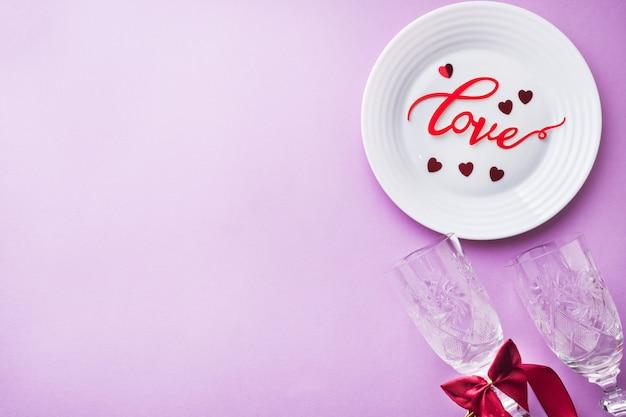 Assiette blanche, deux verres inscription amour sur fond rose. concept de la saint-valentin.
