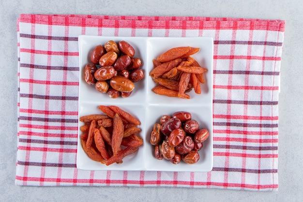 Assiette blanche avec divers délicieux fruits secs sur pierre.