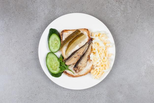 Une assiette blanche avec du pain grillé frit et des sprats