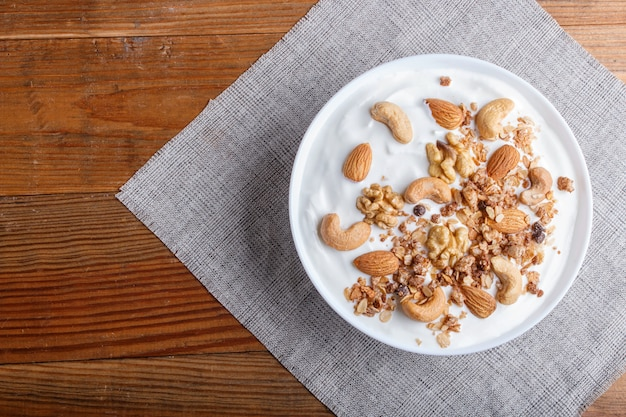 Assiette blanche avec du yogourt grec granola amande noix de cajou sur fond de bois brun