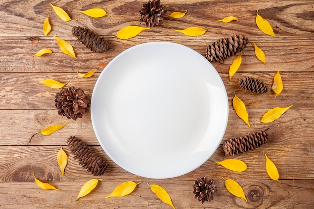 Assiette blanche entourée de pommes de pin et de petites feuilles jaunes sur fond en bois