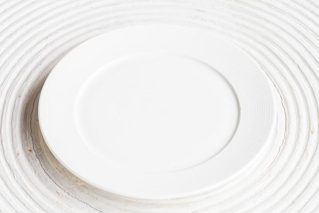 Assiette blanche sur fond de bois blanc