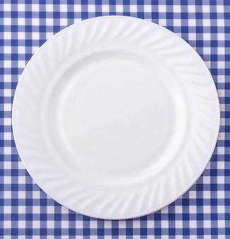 Assiette blanche sur fond de nappe en tissu à carreaux bleus et blancs.
