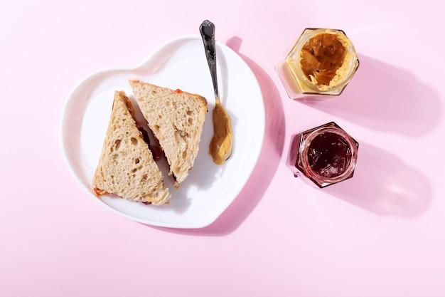 Assiette blanche en forme de coeur avec des sandwichs au beurre d'arachide et gelée de fraises sur rose