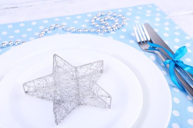 Assiette blanche, fourchette, couteau et décoration de noël sur serviette à pois sur fond de bois