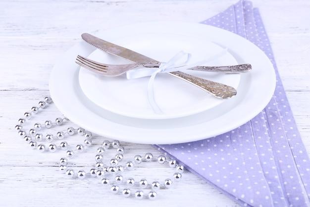 Assiette blanche, fourchette, couteau et décoration de noël sur serviette à pois lilas sur fond de bois