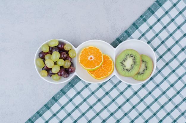Une assiette blanche de fruits frais sur nappe. photo de haute qualité