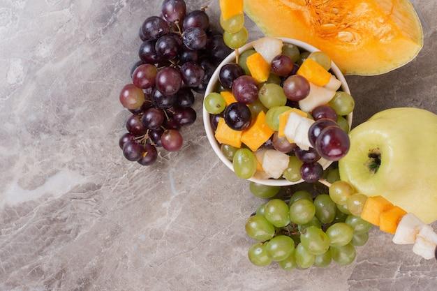 Une assiette blanche de fruits sur une surface en marbre