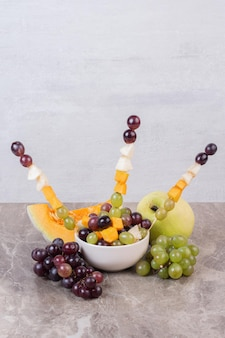 Assiette blanche de fruits sur table en marbre.