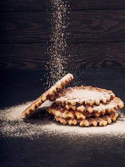 Assiette blanche avec des gaufres belges faites maison, sur le tamisage versé du sucre en poudre sur une collation noire très savoureuse. sucre sur la vieille table en bois. style rustique sombre.