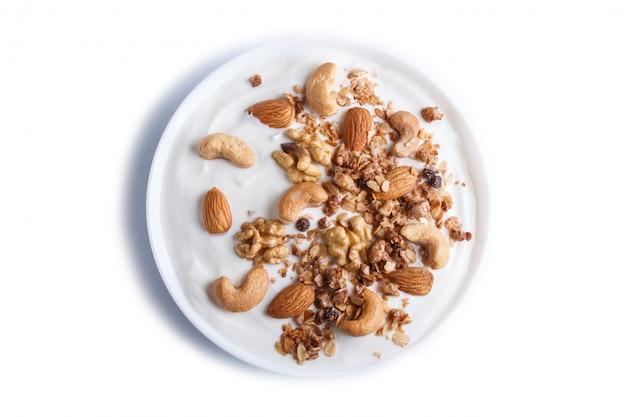 Assiette blanche avec granola de yaourt grec, amande, noix de cajou, noix isolées sur une surface blanche.