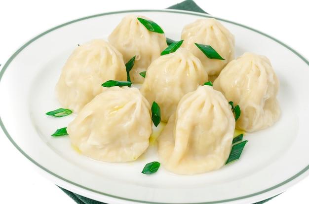 Assiette blanche avec khinkali bouilli, oignons verts.