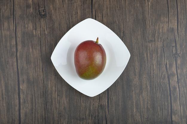 Assiette blanche de mangue fraîche unique placée sur une surface en bois