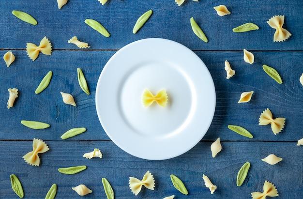 Assiette blanche avec mélange de différentes pâtes sur fond de bois. vue de dessus