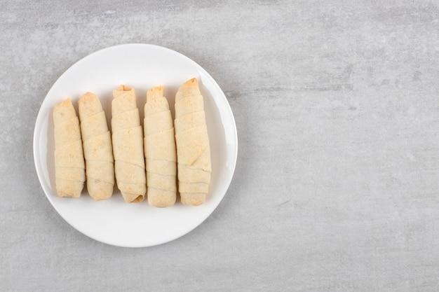 Assiette blanche de mutaki sucré fait maison sur table en pierre.