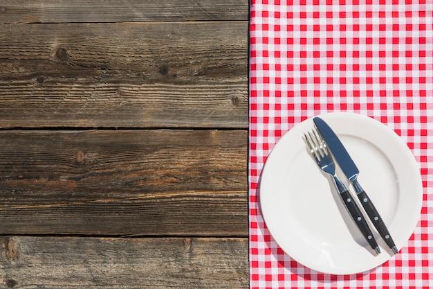 Assiette blanche sur nappe à carreaux et planche de bois texturée