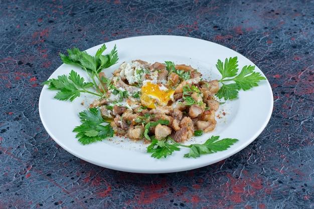 Une assiette blanche d'oeuf au plat avec des herbes .