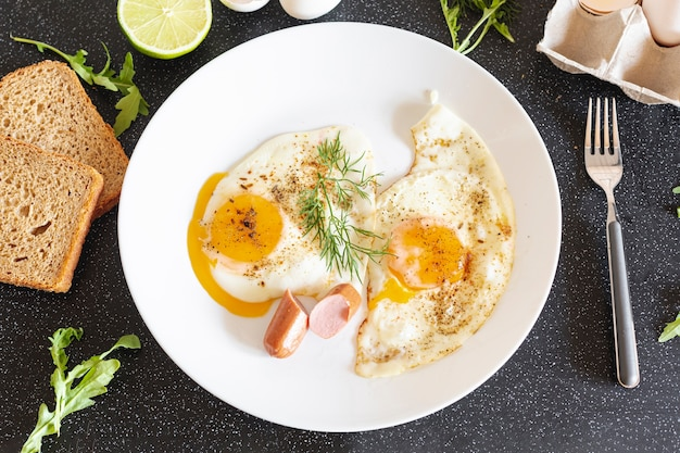 Assiette blanche avec des œufs au plat et du pain sur un tableau noir