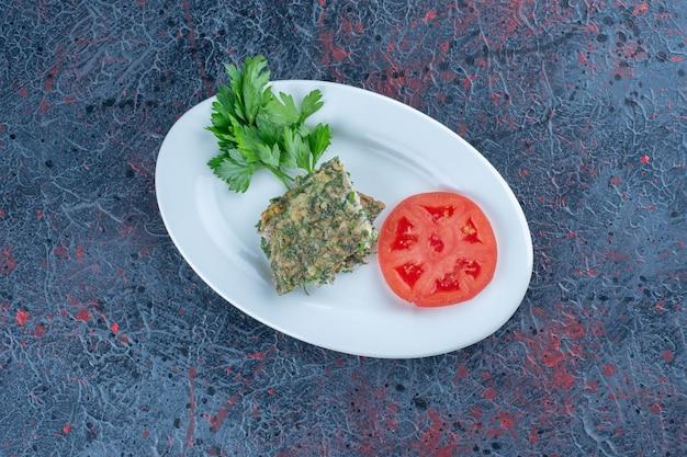 Une assiette blanche d'omelette frite avec des herbes et des tranches de tomate.