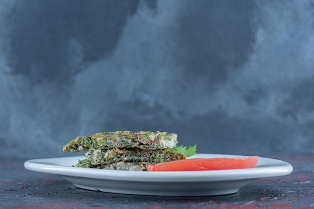 Une assiette blanche d'omelette frite avec des herbes et des tranches de tomate