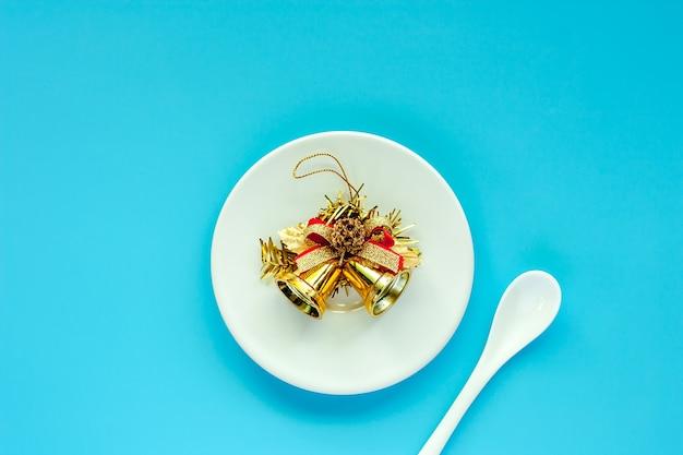 Assiette blanche d'ornements de cloche de ruban de noël avec une cuillère sur fond bleu pour le jour de noël