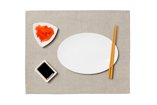 Assiette blanche ovale vide avec des baguettes pour sushi, gingembre et sauce soja sur fond de serviette gris