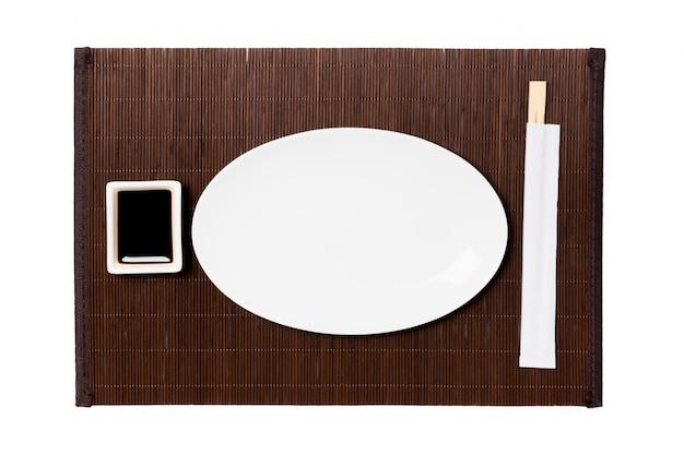 Assiette blanche ovale vide avec des baguettes pour sushi et sauce soja sur fond de tapis de bambou foncé