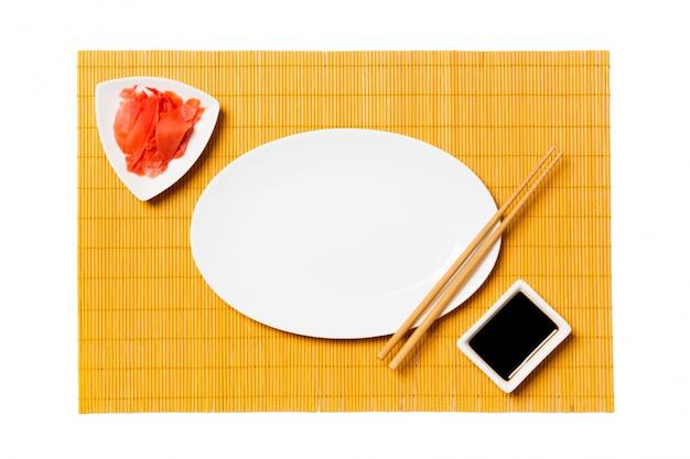 Assiette blanche ovale vide avec des baguettes pour sushi et sauce soja, gingembre sur tapis en bambou jaune
