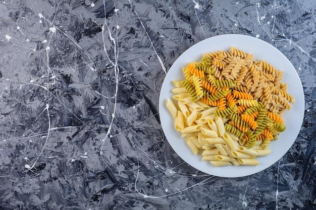 Une assiette blanche de pâtes fusilli multicolores sèches crues avec macaroni penne