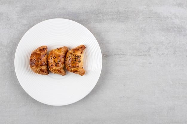 Assiette blanche de pâtisseries savoureuses fraîches sur table en pierre.
